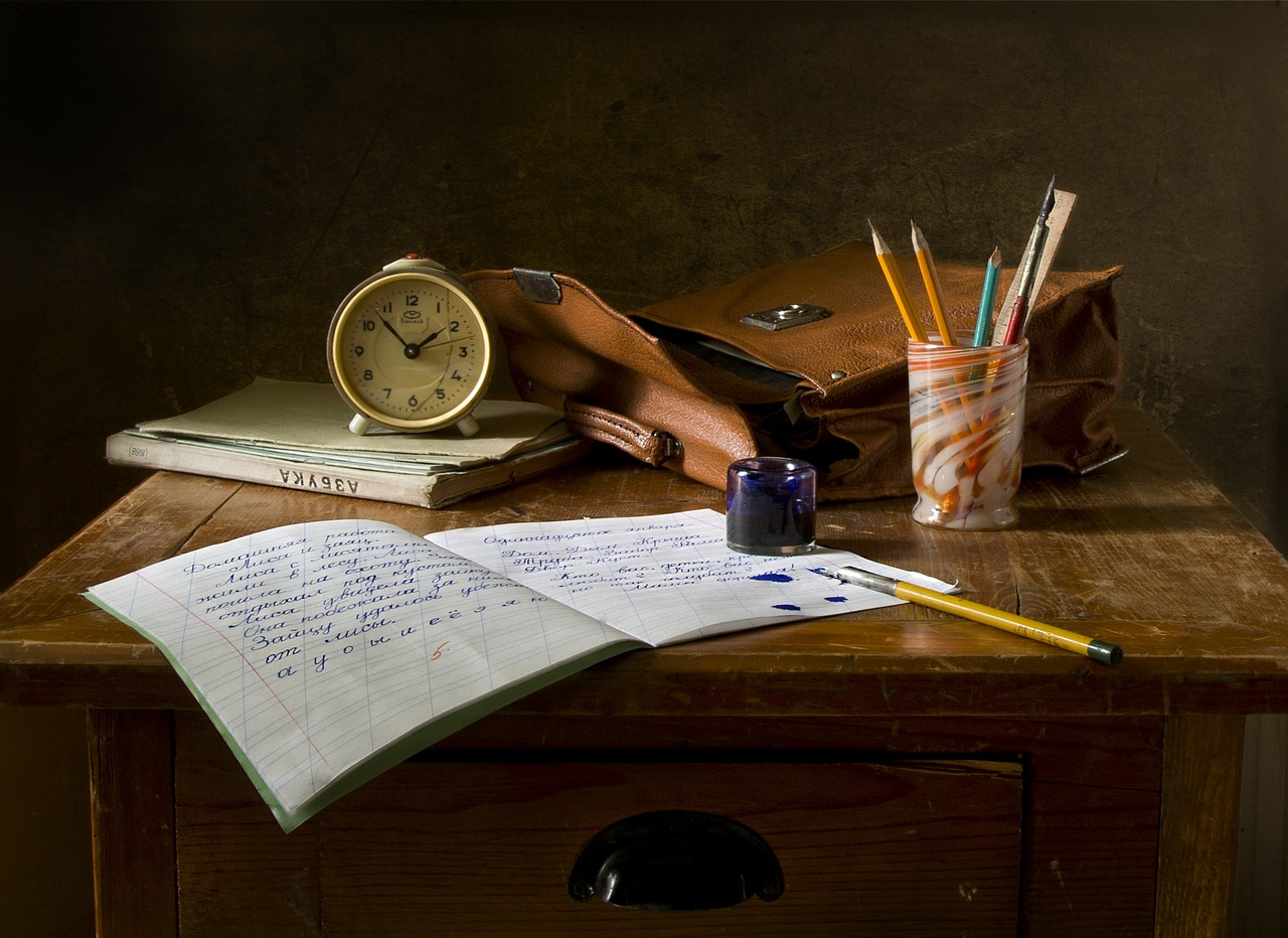 The rules of grammar matter for writers until they don't. The image features an open journal, a clock, a cup of pens, and assorted writing tools rest on a wooden desk.