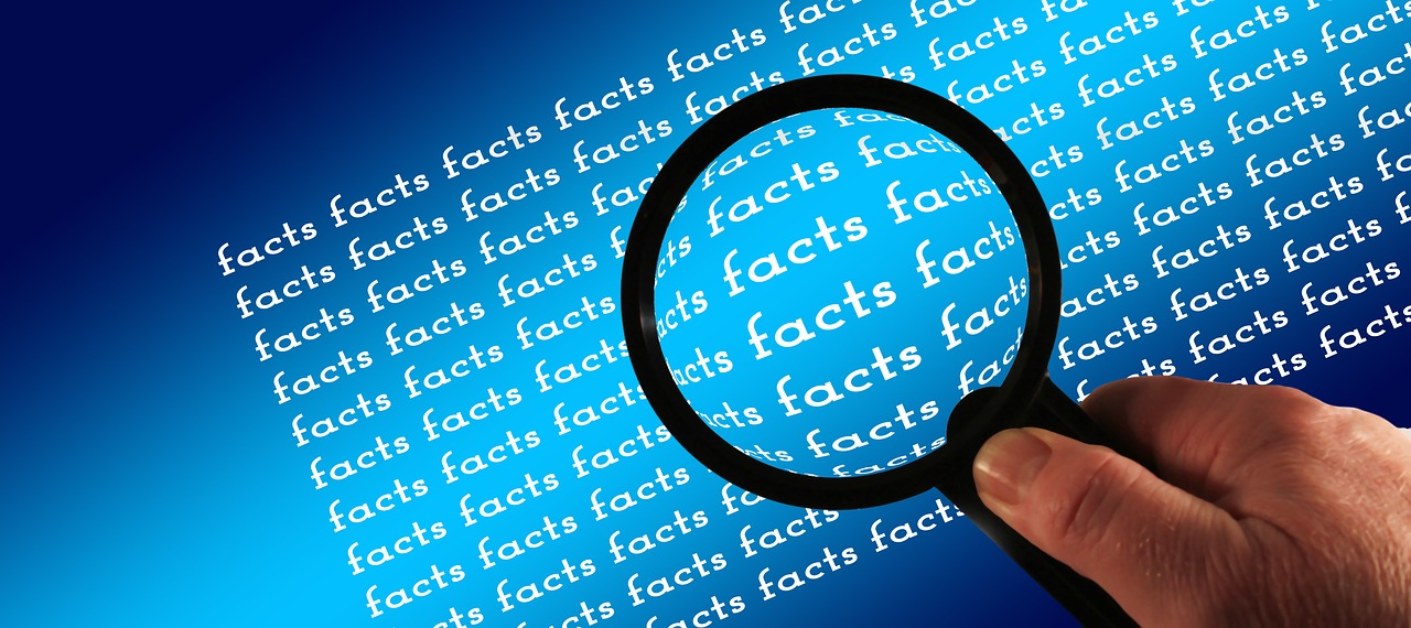 "Magnifying glass over graphic image of ""facts"" repeated on blue surface."