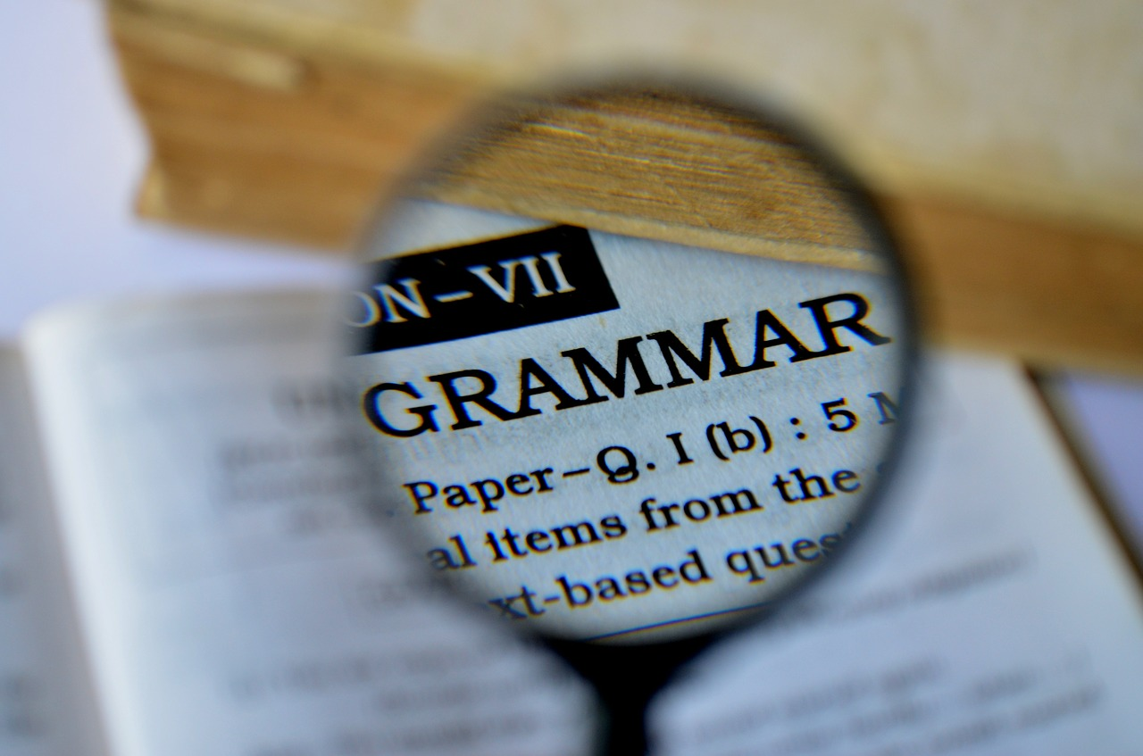 "Grammar mistakes are common. Image features a magnifying glass enhancing the word ""grammar"" in a dictionary."