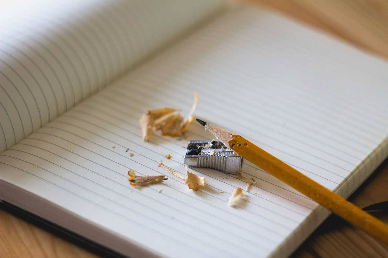 Informative writing should be precise and organized in such a way to help your readers learn new info. Picture shows an open journal with blank pages. On top of one of the pages is a pencil and pencil sharpener.