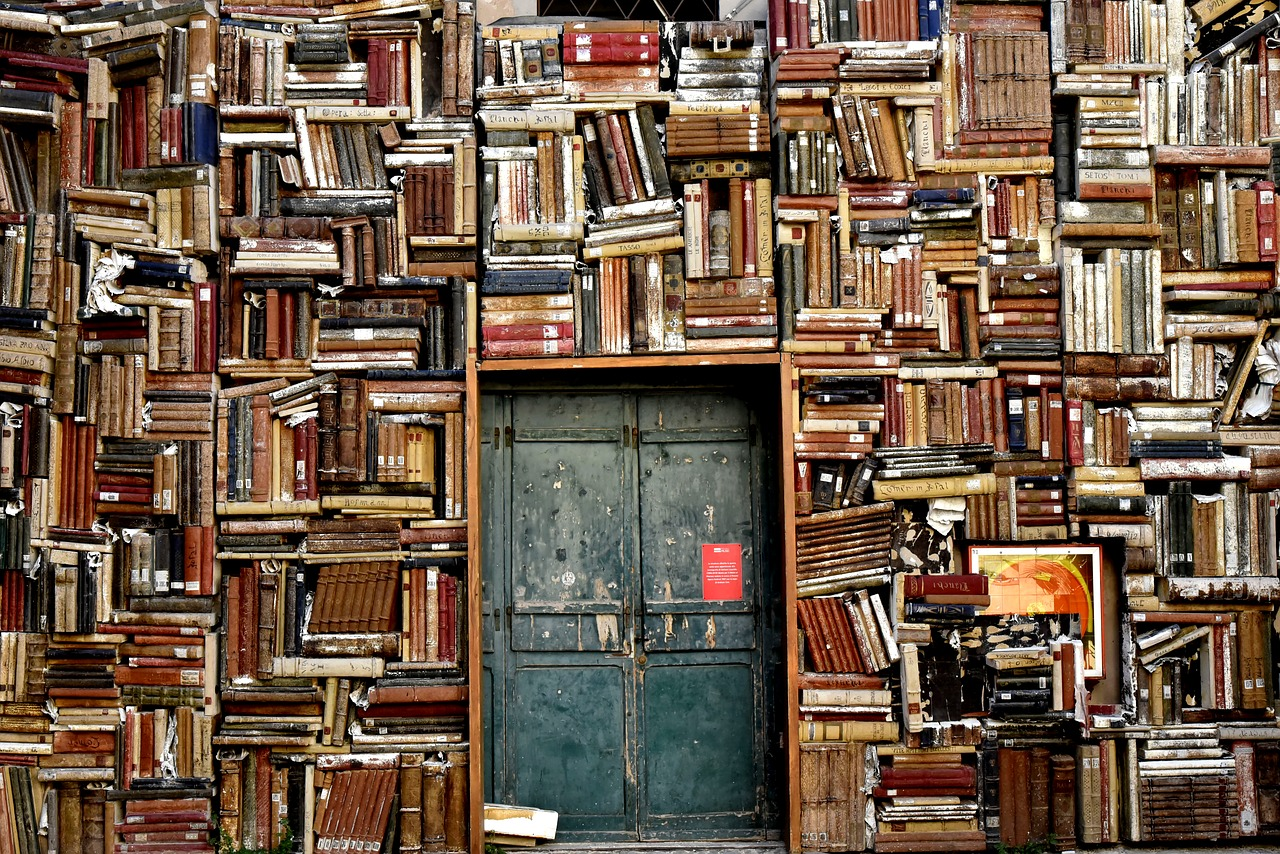 Source evaluation is an important part of researching for your writing project. This image features a door framed by shelves disorderly packed with books.