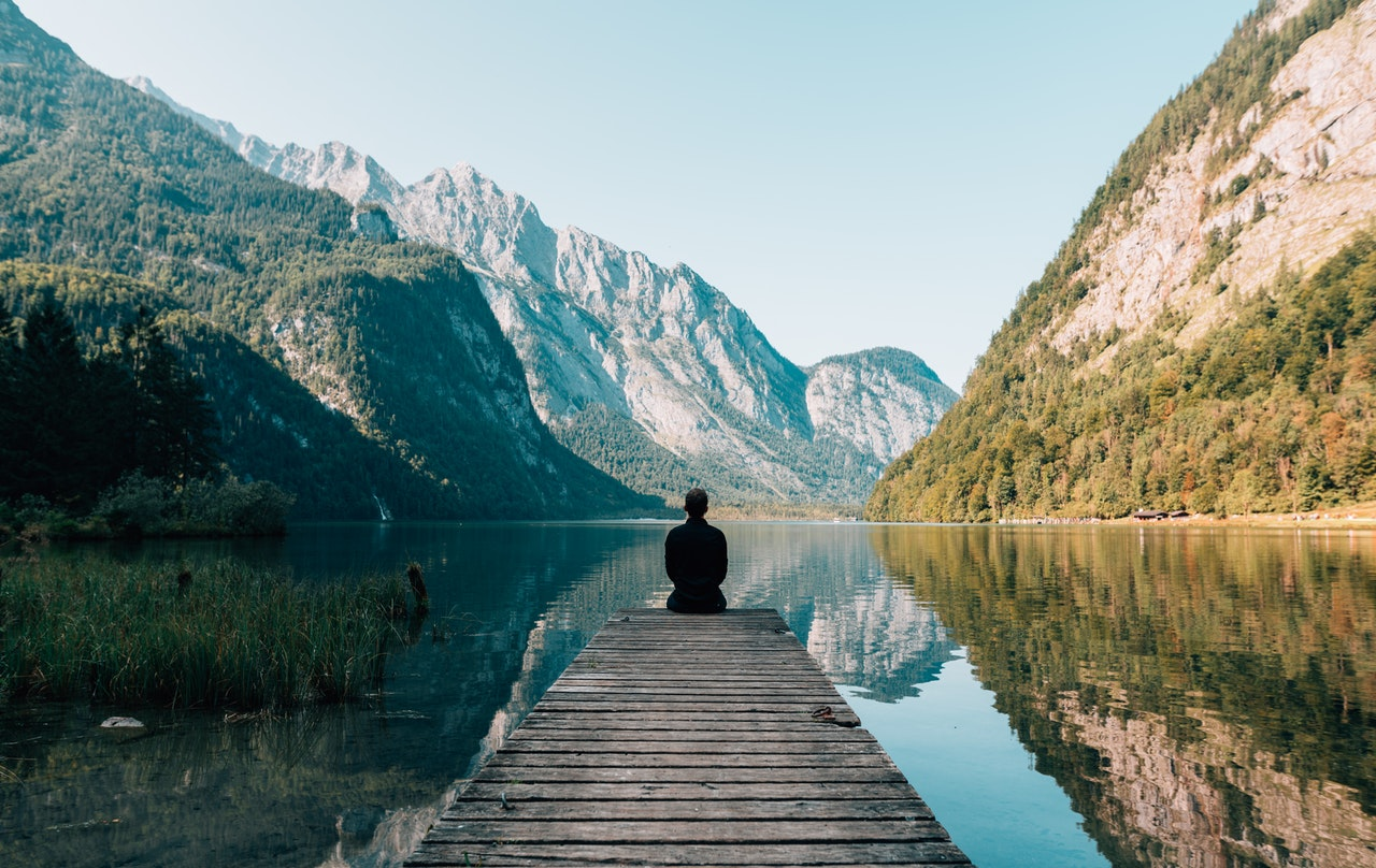 Positive connections happen in all kinds of ways and in all kinds of spaces. Image features a man sitting at the end of a dock, with his back to the camera. Water and mountains stretch out in front of him, and everything in the picture sits under a bright blue sky.